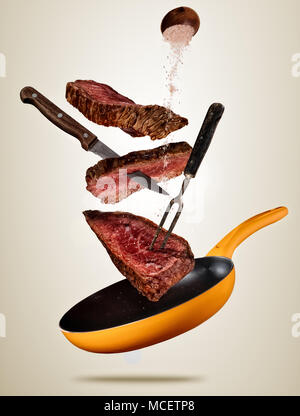 Flying pieces of beef steaks from pan, isolated on colored background. Concept of flying food, very high resolution image - Stock Photo