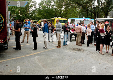 Customers stand in line to order meals from several food trucks during their lunch hour, at 'Food Truck Thursday' on October 16, 2014 in Atlanta, GA. - Stock Photo