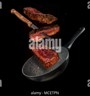 Flying pieces of beef steaks from pan, isolated on black background. Concept of flying food, very high resolution image - Stock Photo