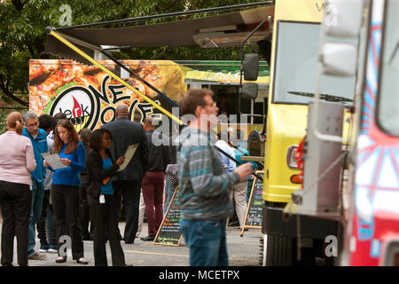 Customers stand in line to order meals from popular food trucks during their lunch hour, at 'Food Truck Thursday' on October 16, 2014 in Atlanta, GA. - Stock Photo