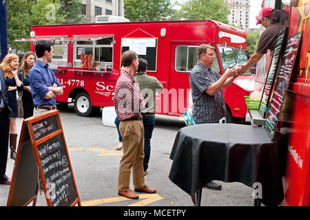 Customers stand in line to order meals from a popular food truck during their lunch hour, at 'Food Truck Thursday' on October 16, 2014 in Atlanta, GA. - Stock Photo