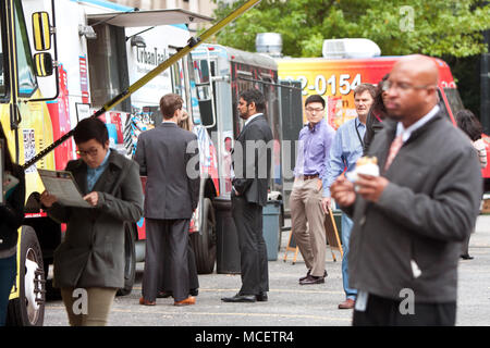 Customers stand in line to order meals from food trucks during their lunch hour, at 'Food Truck Thursday' on October 16, 2014 in Atlanta, GA. - Stock Photo