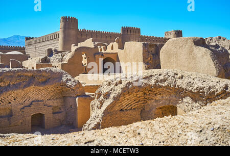 Ruins of the ancient buildings in archaeological site and the massive walls and watchtowers of Rayen castle on the background, Iran. - Stock Photo