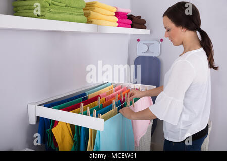 Side View Of A Young Woman Hanging Wet Clothes On In Laundry Room - Stock Photo