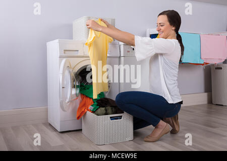 Happy Young Woman Looking At Cleaned Yellow Tshirt After Washing In Washing Machine - Stock Photo