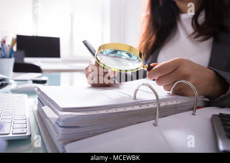 Close-up Of A Businesswoman's Hand Checking Bill Through Magnifying Glass At Workplace - Stock Photo