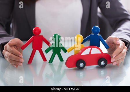 Close-up Of A Businessperson's Hand Protecting Multi Colored Human Figures And Red Car - Stock Photo