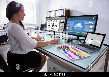 Close-up Of A Female Designer Working On Multiple Computer At Workplace - Stock Photo