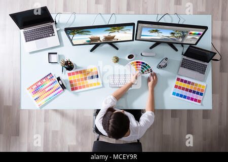 High Angle View Of A Female Designer Using Color Swatch While Working On Multiple Computer - Stock Photo