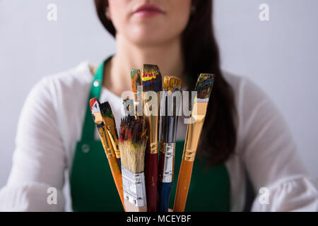 Close-up Of Various Paintbrushes In Front Of Female Artist - Stock Photo