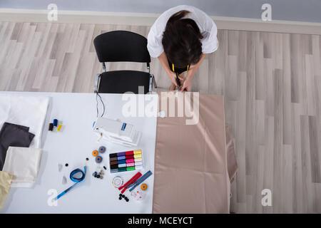 Young Female Fashion Designer Cutting Cloth With Scissors On Desk In Studio - Stock Photo