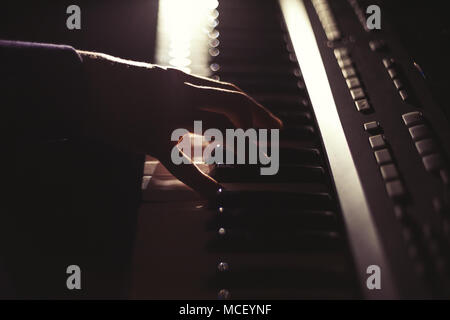 Playing on synthesizer keyboard in the dark - Stock Photo