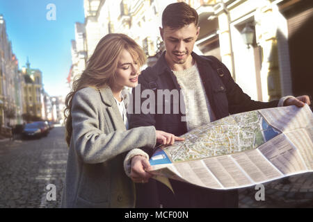 Couple of young tourists reading a map in the city - Stock Photo