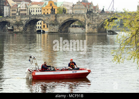 Prague - April 15: 2 firefighters sits in their boat and makes their training sail in the close neighborhood of Charles Bridge, on April 15, 2018 in P - Stock Photo