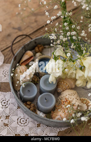 Coastal or rustic interior design concept. Table centerpiece with metal tray filled with candles, seashells and flowers. - Stock Photo