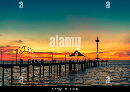 People walking along Brighton Jetty at sunset on summer evening - Stock Photo