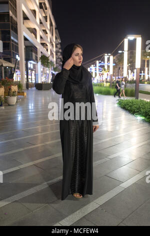 Muslim woman wearing in a hijab walks in the night city. - Stock Photo