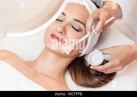 Close-up of a beautiful woman relaxing during facial treatment in beauty center - Stock Photo
