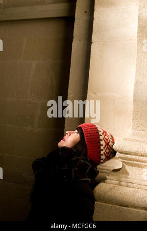 attractive middle-aged french woman with bobble hat looks up towards ceiling inside old church - Stock Photo