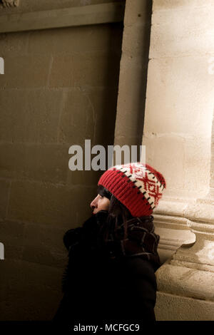 attractive middle-aged french woman with bobble hat inside old church attractive middle-aged french woman with bobble hat inside old church - Stock Photo