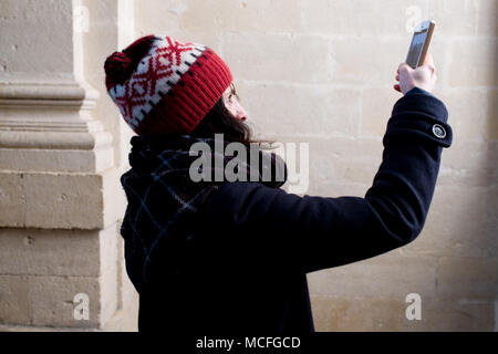 attractive middle-aged french woman with bobble hat takes a photo with her smartphone inside old church - Stock Photo