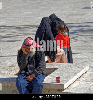 Amman, Jordan, March 11, 2018: A traditionally dressed Bedouin sits on a bench on stone and talks on the phone, while on the other side two women in b - Stock Photo