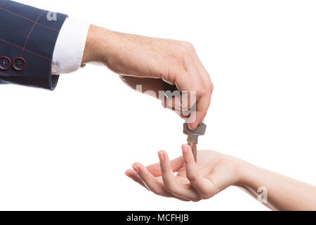 Close-up of realtor or real estate agent hand offering keys to buyer as new housing aggrement concept isolated on white background - Stock Photo