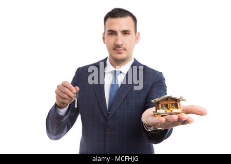 Real estate agent or realtor holding house and home keys as accommodation housing offer concept isolated on white background - Stock Photo