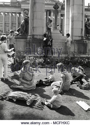 Members of the public relaxing, playing and some really enjoying themselves in the sunshine around the cenotaph Bolton in the late 1970s or early 1980s, on Victoria Square with the Town Hall in the background. Bolton, North West England UK. photo DON TONGE photographer - Stock Photo