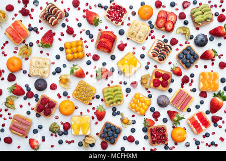 Colourful square fruit tarts on a white background - Stock Photo
