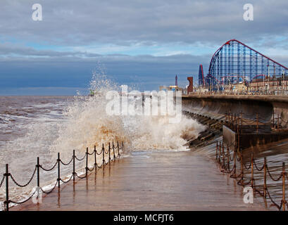 Waves splashing against Blackpool's sea defence, making a picturesque scene,  with the big one, Blackpool Pleasure Beach, in the background - Stock Photo