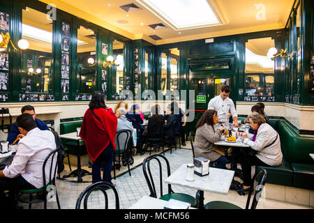 People eating churros at a cafe, Interior of Chocolateria San Gines - the oldest churreria and chocolateria in Madrid, Spain - Stock Photo