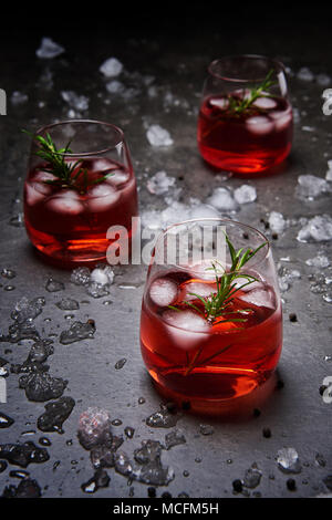Pomegranate cocktail with ice and rosemary surrounded with crushed ice on the black concrete background. - Stock Photo