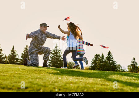 American soldier is meeting his two daughters outdoor. Two little girls with usa flags are running to their hero father came back from us army. - Stock Photo