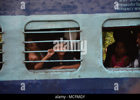 Family travelling on a train in India and the boy peering out of the barred window from the carriage
