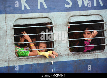 A family seen through the bars of a window on a train in India, Mumbai bound