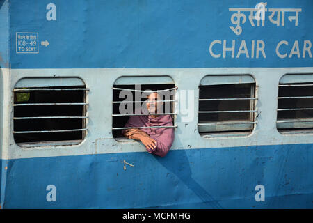 Man looking out of the window on a passing train in India