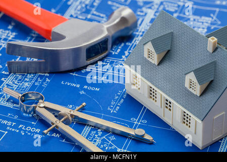 Blueprints with a Model House and Construction Tools. - Stock Photo