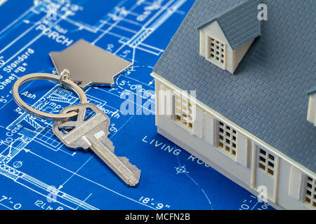 Blueprints with a Model House and Keys to Home. - Stock Photo