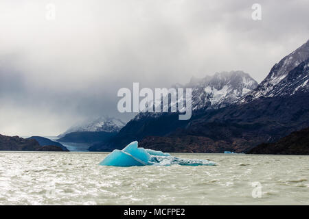 Small iceberg floating during low tide in Glacier Gray, beautiful mountain range with snow in the background. Torres del Paine, Chile. - Stock Photo