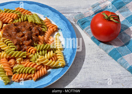Delicious homemade colorful pasta whit meat sauce and fresh tomato at white wooden background - Stock Photo