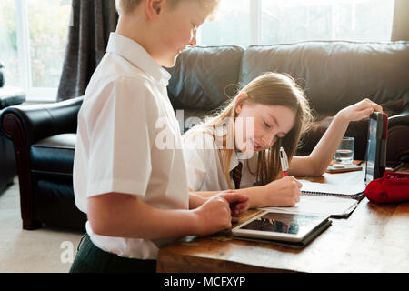 Little boy and his sister are studying together at home. They both have a digital tablet and the girl is writing in a planner. - Stock Photo