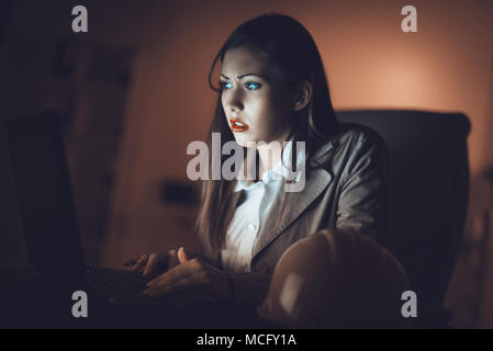 Worried lonely young woman looking at lighted screen of a laptop in night at the home. She is tired because working late. - Stock Photo