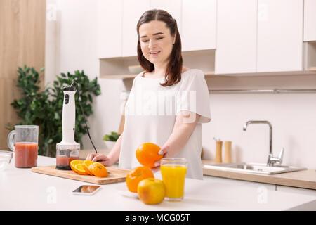 Ambitious beautiful woman making healthy breakfast - Stock Photo