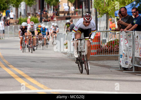 Duluth, GA, USA - August 2, 2014:  A male cyclist separates himself from a group of racers competing in the Georgia Cup Criterium event. - Stock Photo