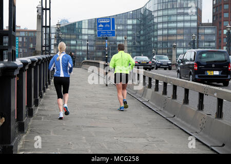 Man and woman wearing lycra back view rear jogging over Lambeth Bridge in London England UK  KATHY DEWITT - Stock Photo