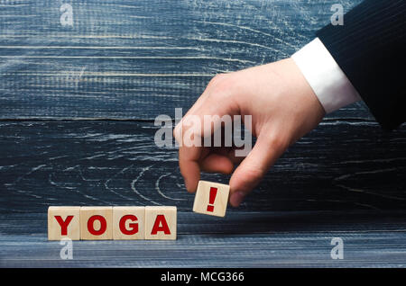 The hand holds a cube with the exclamation point symbol for the word yoga. Doing sports, exercises, art of yoga. A healthy lifestyle, without stress.  - Stock Photo