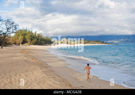 A lone woman running on Baldwin Beach early in the morning. Maui, Hawaii. (The sand tide is out.) - Stock Photo