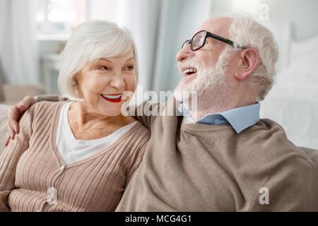 Cheerful elderly man hugging his wife - Stock Photo