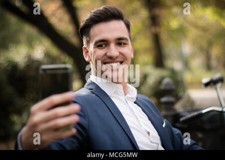 Young attractive and happy businessman taking a selfie with his smartphone in the park. - Stock Photo